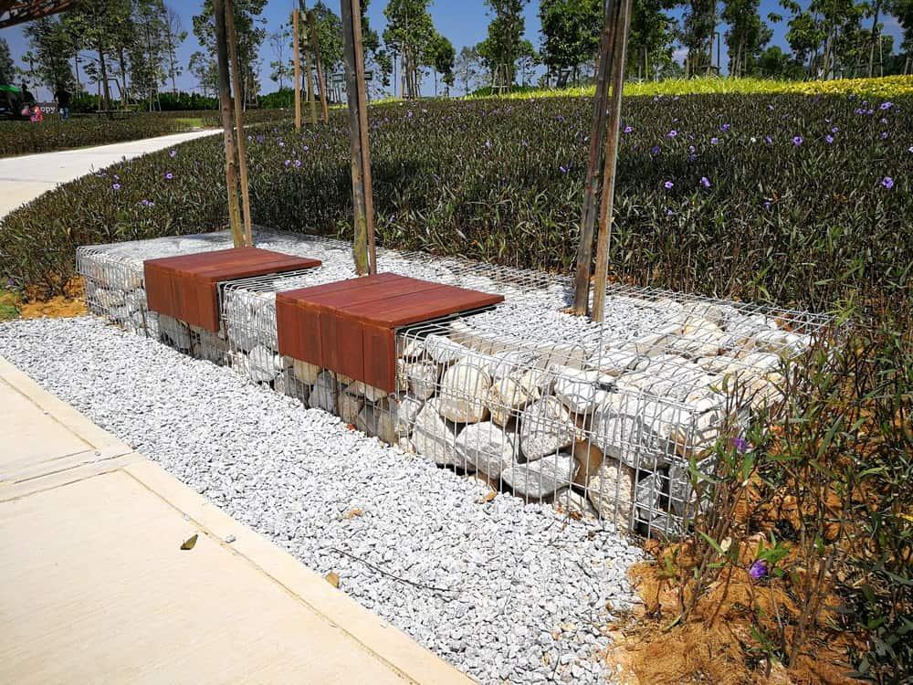 Large rock gabion bench on side of walkway.