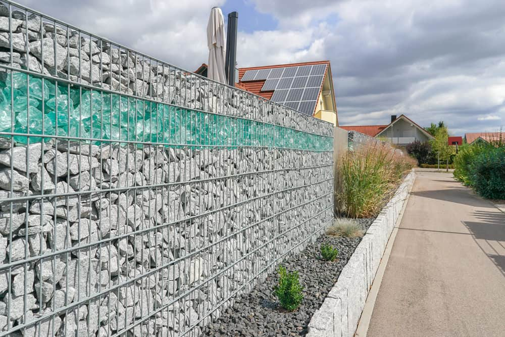 Large gray crushed limestone gabion fence with layer of blue rock around permiter of a house.