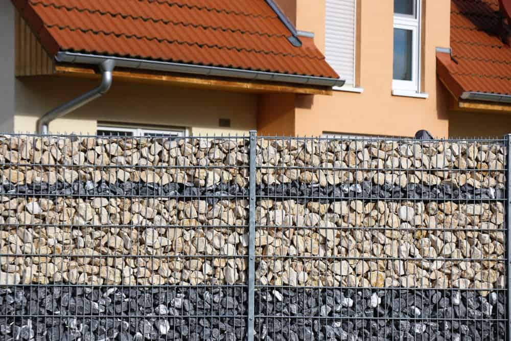 Close up of a crushed rock gabion fence.