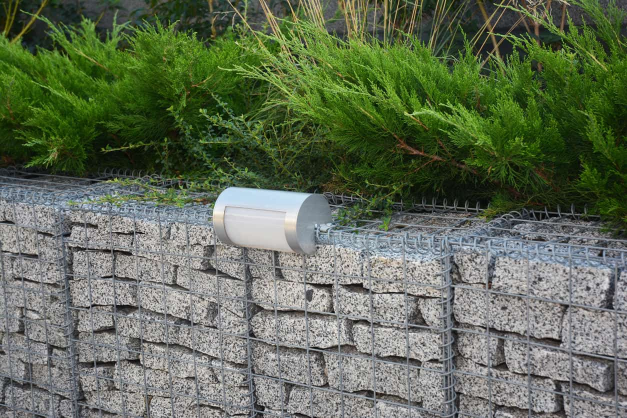 Close up of gray gabion retaining wall with outdoor lights.