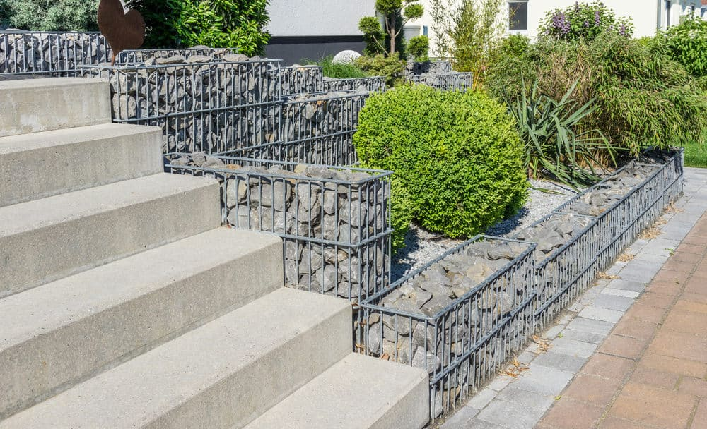 Attractive gabion retaining wall in front yard supporting several levels of gardens.