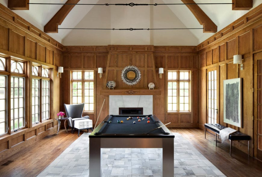 This is a bright and homey game room with a wooden pool table in the middle of the light gray area rug of the hardwood flooring. This wooden flooring extends to the elegant wooden finish of the walls dominated by tall bright windows and topped with a white cathedral ceiling.