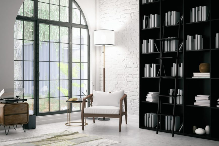 This home boasts an elegant black bookshelf with a ladder. The white brick walls match the white floors perfectly.