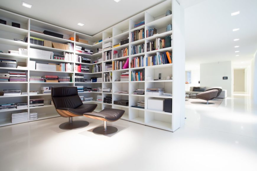 White home library with featuring multiple white shelves and a cozy seat with a footrest.