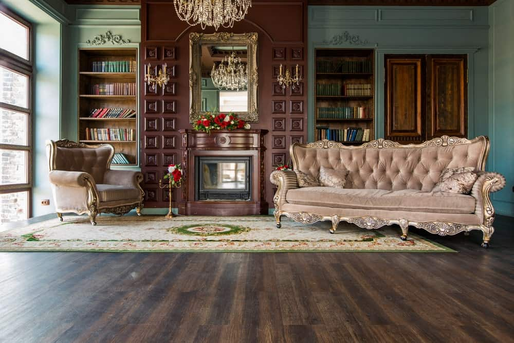 An elegant living room featuring luxurious seats and rug along with a fireplace. There are built-in bookshelves housing multiple books. The room is lighted by a glamorous chandelier.