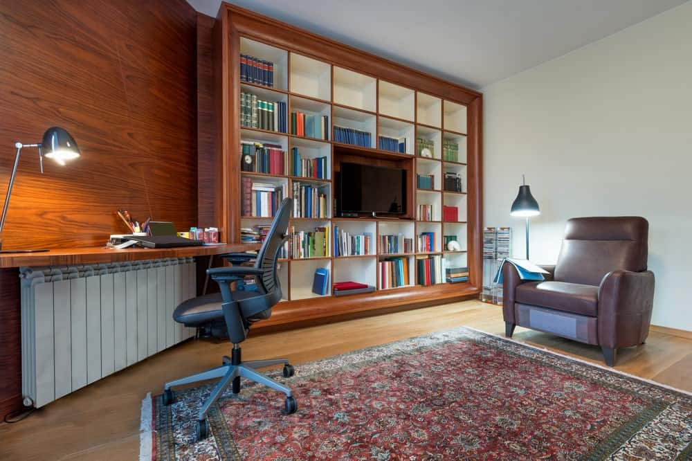 A home library with a classy club chair and a rug set on the hardwood flooring. The room also features a built-in desk matching the stylish wooden wall.