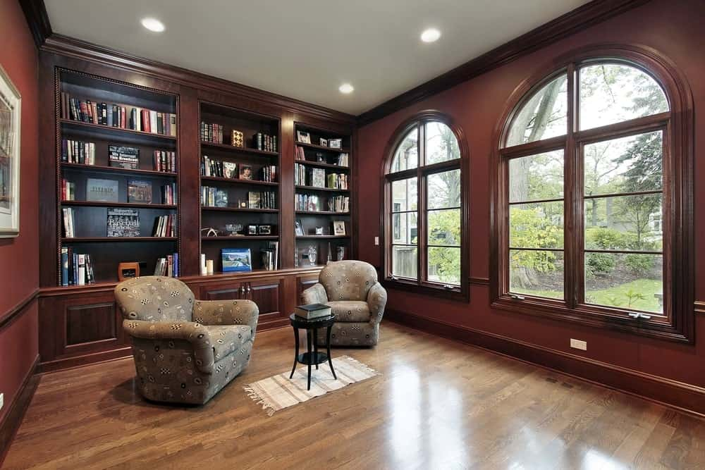 A classy home library with elegant seats and a coffee table set on the hardwood flooring. The walls look perfect together with the built-in shelves.