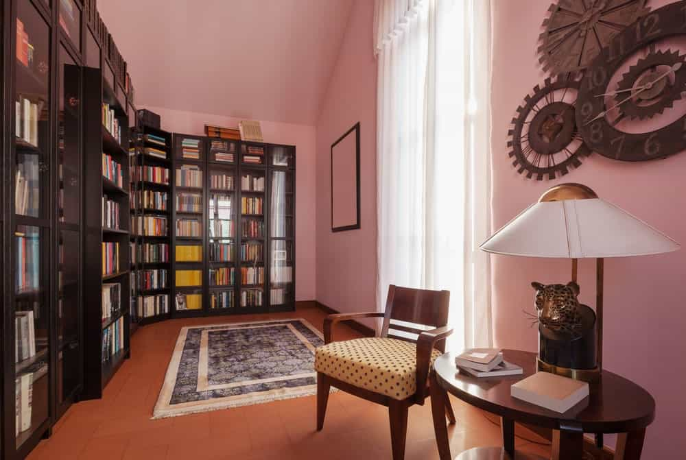 This home library features pink walls and espresso-finished bookshelves. The brown floors look great together with the room's style.