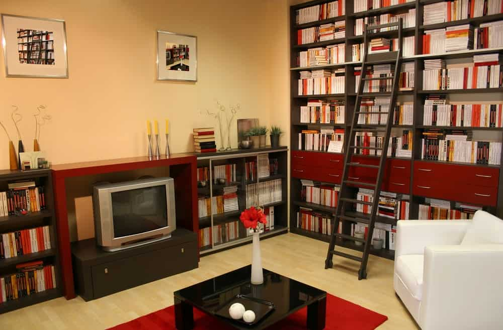 A modish home library with stylish bookshelves and an elegant black center table on top of a red rug set on the hardwood flooring.