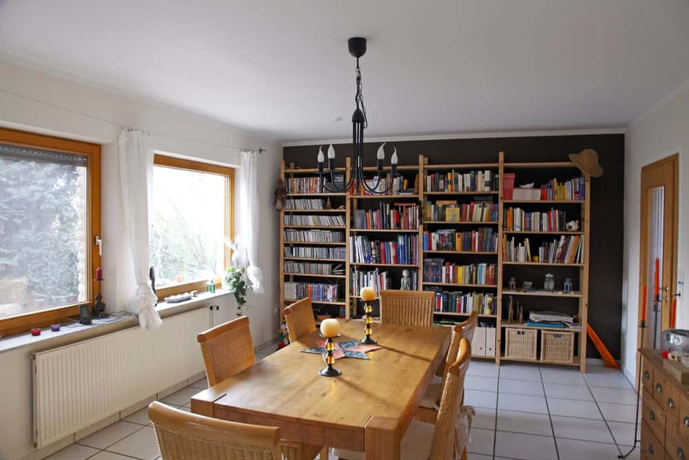 This home library features multiple bookshelves on the side and a rectangle dining table set on the tiles flooring.