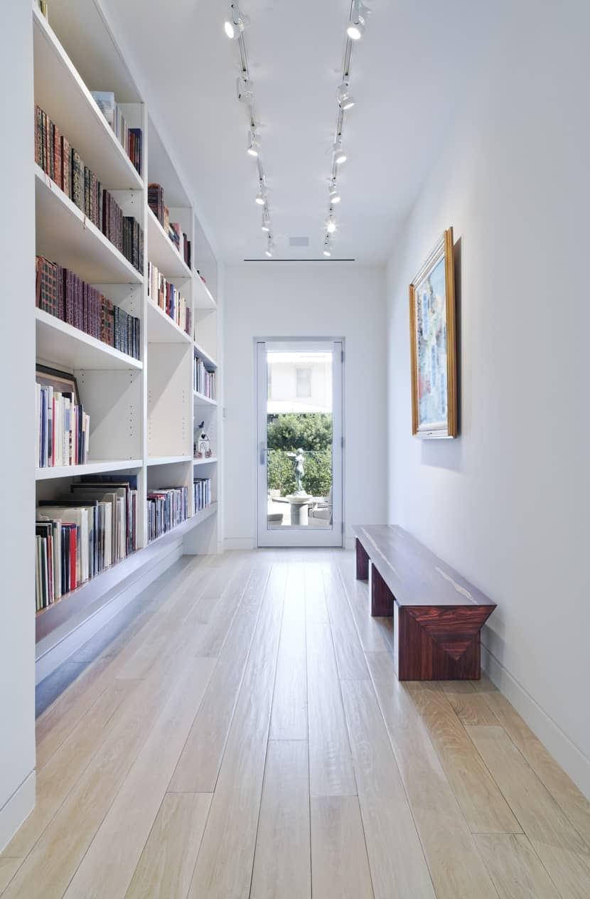 A white home library with multiple bookshelves and hardwood flooring and a bench seating lighted by track ceiling lights.