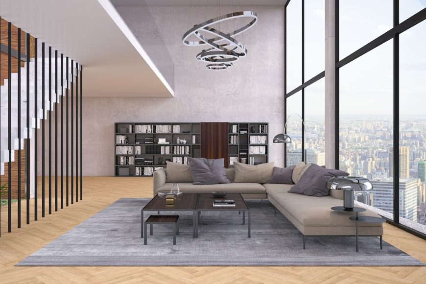 Large formal living room offering a cozy sofa set on top of a stylish gray rug covering the herringbone hardwood flooring. The room also features handsome bookshelves.