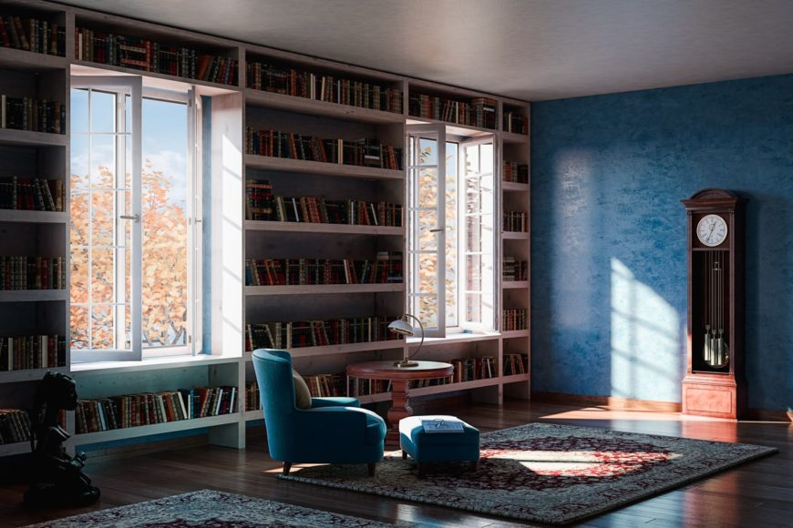 Large home library with stylish built-in bookshelves and blue walls matching the blue seat. The rugs look perfect together with the hardwood flooring.