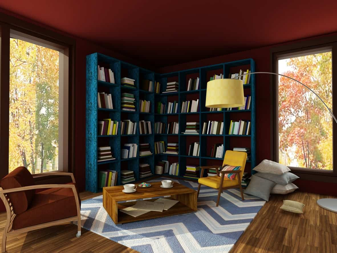 This home library features stylish blue bookshelves surrounded by red walls. The blue and white rug looks perfect together with the hardwood flooring.