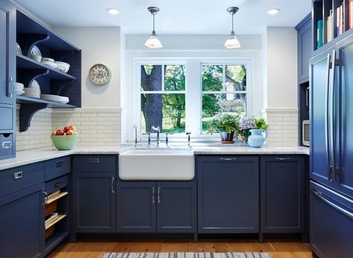 Deep rich blue cabinets with white farmhouse sink, white subway tile backsplash and white walls/ceiling