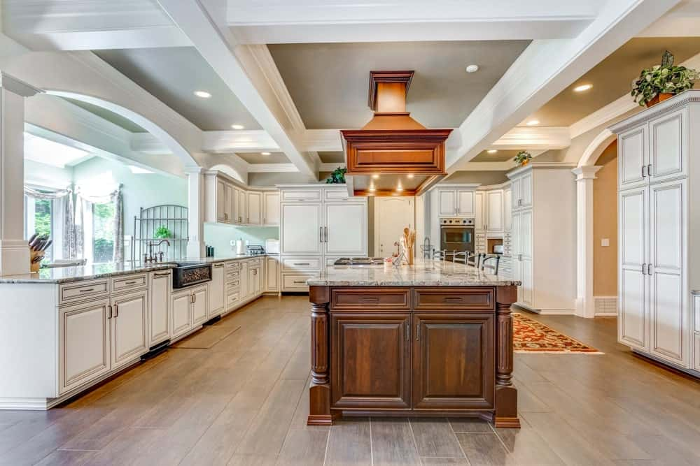 A large kitchen with a stunning coffered ceiling and hardwood flooring. It also offers a large center island with space for a breakfast bar.