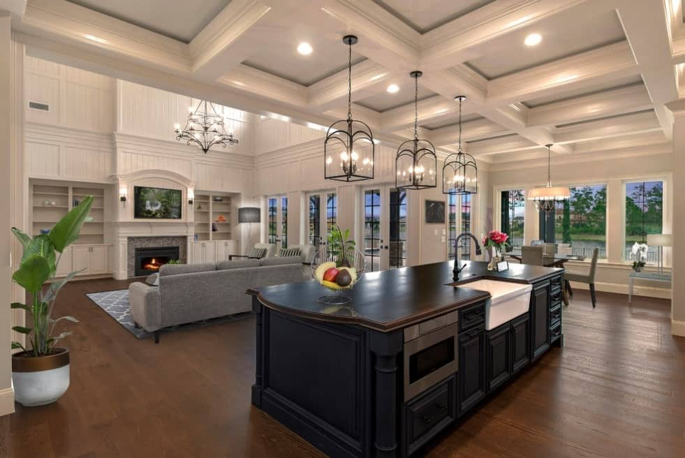 A great room with a modern living set with a fireplace and a TV on top, a square dining nook on the side and a single wall kitchen with a large and stylish center island.