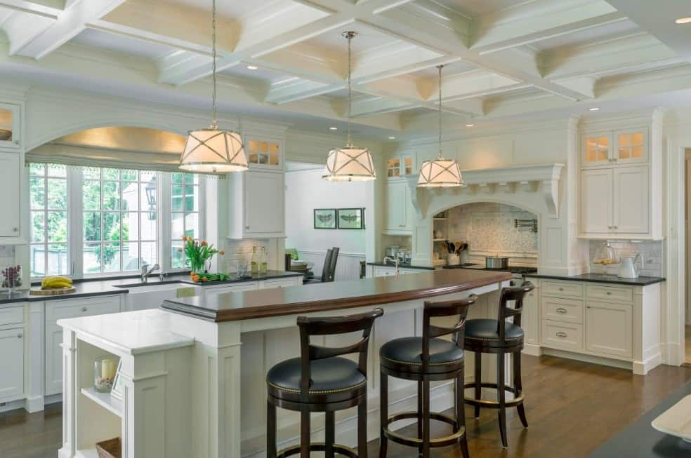 Large kitchen area featuring a breakfast bar lighted by pendant lights hanging from the white coffered ceiling.