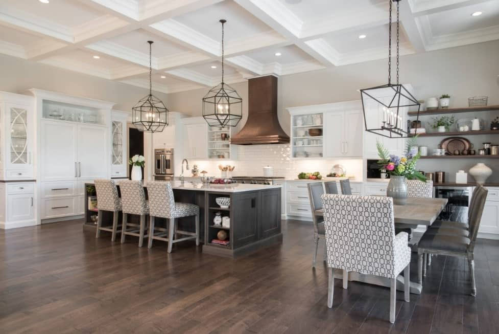 Large dine-in kitchen featuring a white coffered ceiling matching the white cabinetry and kitchen counters, along with a breakfast bar and a dining table set for eight.