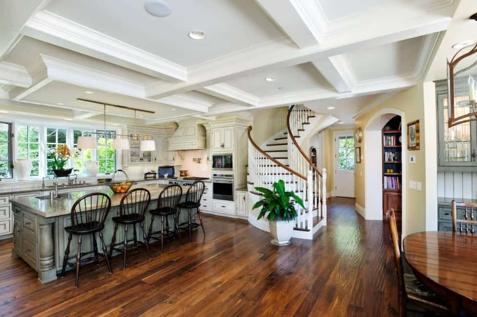 Large kitchen area featuring hardwood flooring and a white coffered ceiling. The kitchen has a stylish island providing space for a breakfast bar lighted by pendant lights.