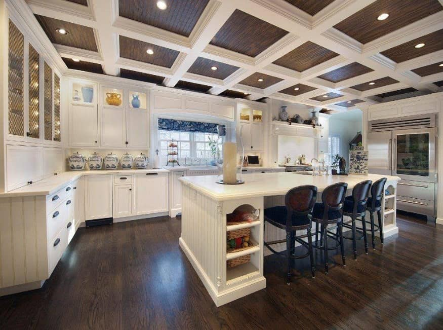 A kitchen featuring a white breakfast bar counter with classy bar stools set on the room's hardwood floors. The kitchen's coffered ceiling looks very attractive.