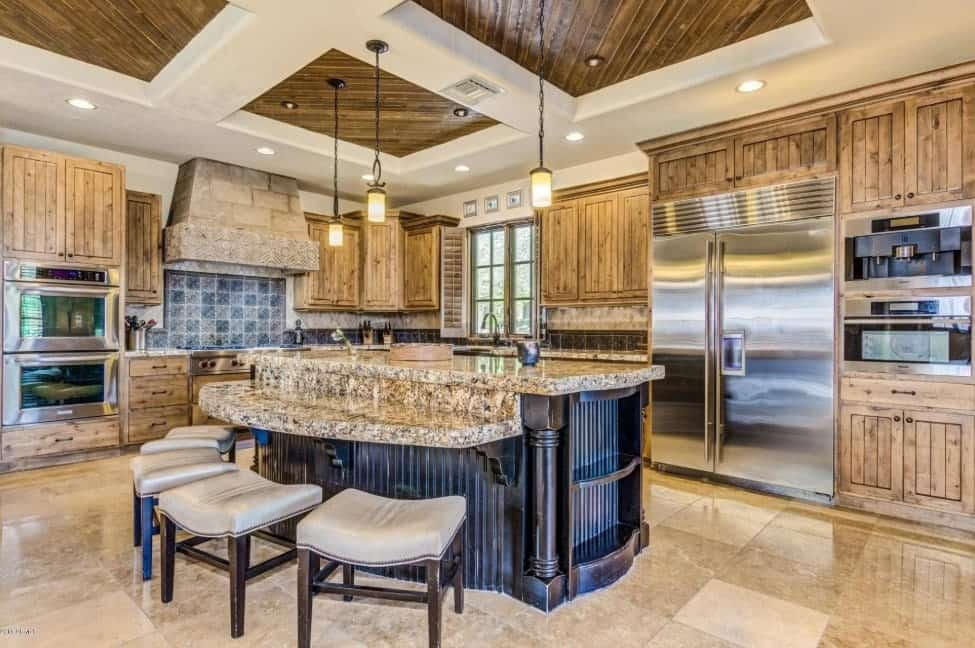 A kitchen boasting rustic cabinetry and kitchen counters. It also features a very stylish center island with a stunning countertop.