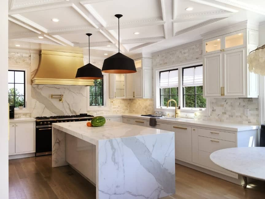 This kitchen boasts tiles backsplash and a marble countertop on the waterfall-style center island lighted by stylish black pendant lights.