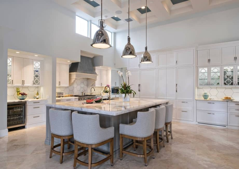 A kitchen featuring tiles flooring and a tall ceiling, along with white cabinetry and kitchen counters with marble countertops. The breakfast bar is lighted by pendant lights.