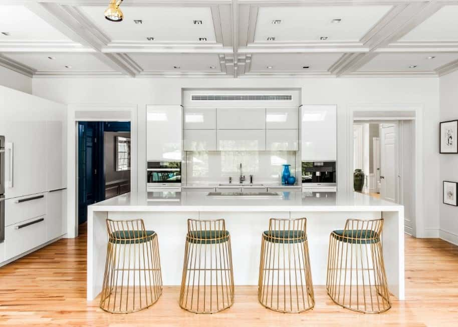 Modern kitchen with white walls and ceiling, along with a waterfall-style island with space for a breakfast bar.