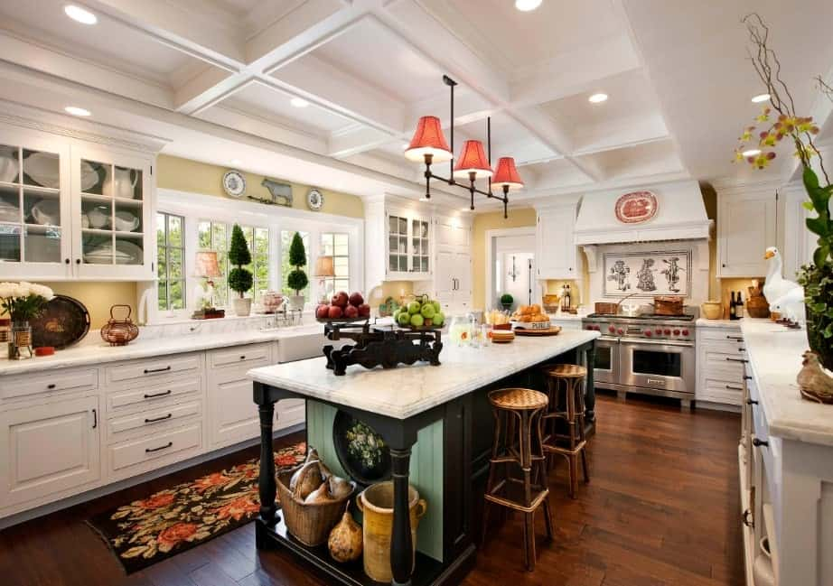 This kitchen boasts white cabinetry and kitchen counters with marble countertops. The room also has hardwood flooring and a white coffered ceiling.