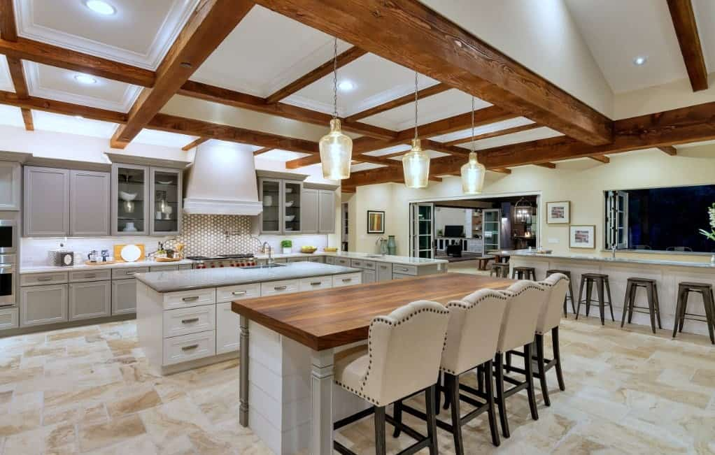 Large kitchen area with a coffered ceiling and classy tiles flooring. There's a breakfast bar lighted by charming pendant lights.