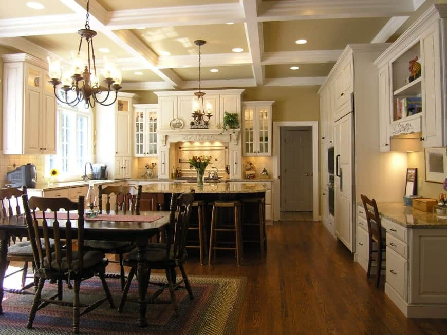 An L-shape kitchen with a breakfast bar and a dining table set for four, lighted by a fabulous chandelier.