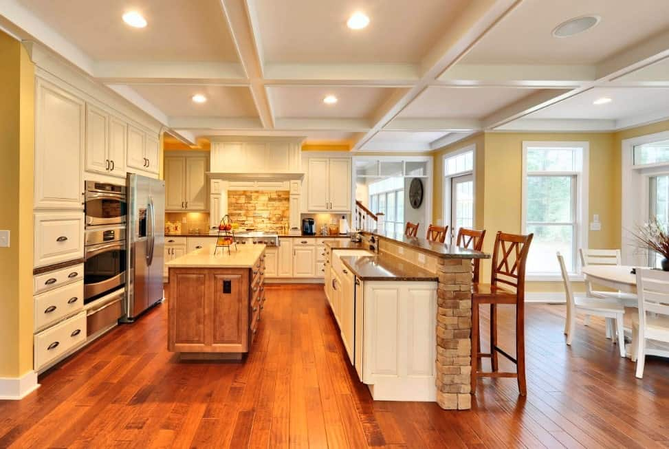 Large L-shape kitchen featuring a white coffered ceiling matching the white cabinetry and kitchen counters. There's a breakfast bar as well equipped with tall bar stools set on the home's hardwood floors.