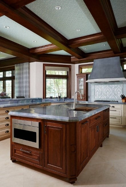 A close up look at this kitchen's center island set on the room's tiles flooring. The island's base matches the coffered ceiling.