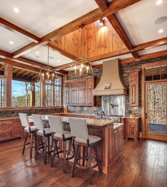 Rustic kitchen area featuring hardwood flooring and a coffered ceiling, along with a breakfast bar lighted by gorgeous ceiling lights.