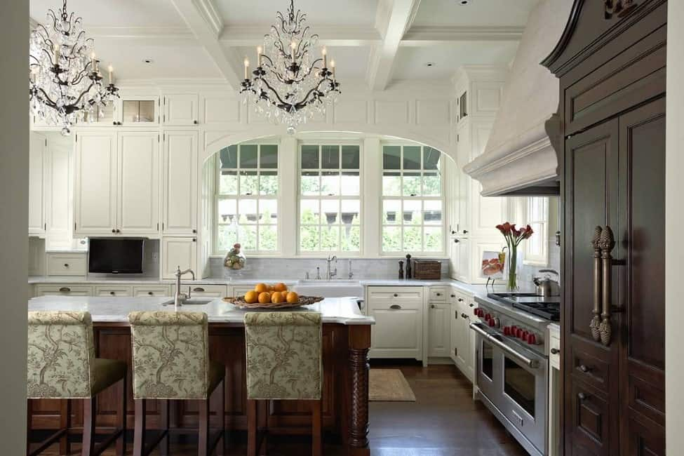 A kitchen with white cabinetry and kitchen counters, along with a breakfast bar lighted by a pair glamorous chandeliers hanging from the white coffered ceiling.
