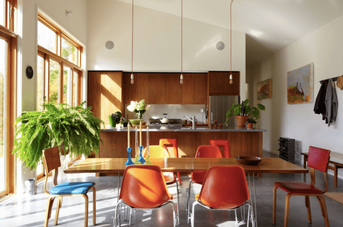 A dine-in kitchen featuring pendant lights hanging from the high shed ceiling.