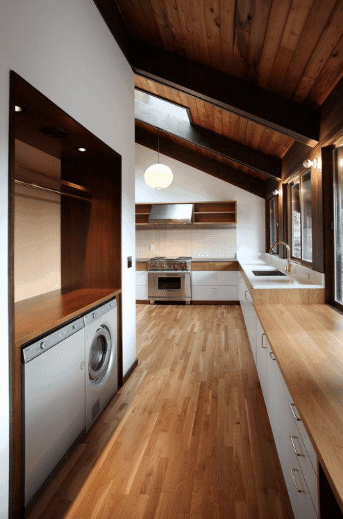 A stylish kitchen and laundry combo featuring hardwood flooring matching the wooden shed ceiling with beams.