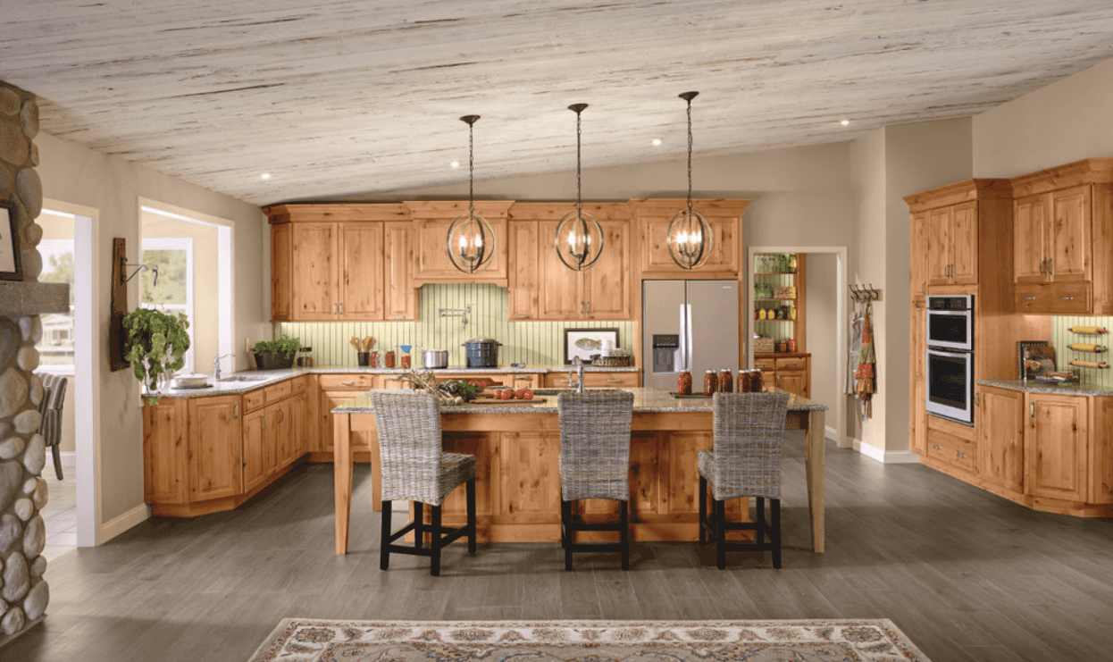 Large kitchen featuring a breakfast bar lighted by pendant lights hanging from the shed ceiling. The gray hardwood flooring adds style to the area.