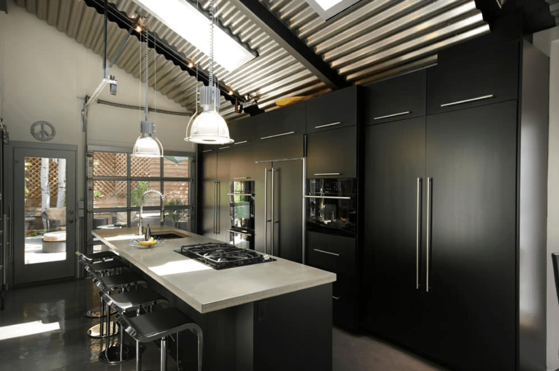 The black shade surrounding this kitchen adds elegance to the room. The stylish breakfast bar is lighted by pendant lights hanging from the shed ceiling.