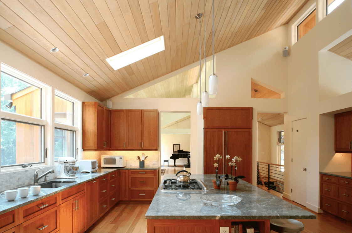 Spacious kitchen with a large center island with gray marble countertop lighted by pendant lights hanging from the wooden shed ceiling with a skylight.
