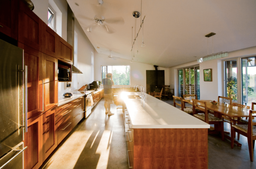 a large dine-in kitchen featuring white shed ceiling and multiple pendant lights. The long center island boasts white marble countertop. There's a large dining table set made of hardwood as well.