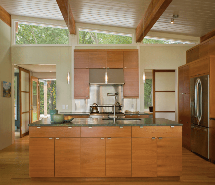 This kitchen boasts cherry-finished cabinetry and kitchen counters with black granite countertops. The high shed ceiling looks marvelous too.
