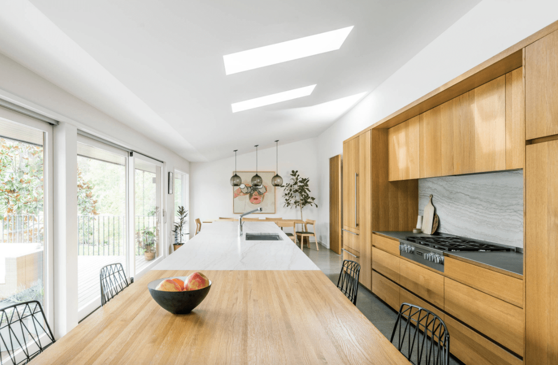 A classy kitchen featuring a white shed ceiling with skylights. The kitchen features walnut-finished cabinetry and kitchen counters.