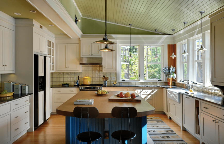 This kitchen offers multiple pendant lights hanging from the shed ceiling. There's a breakfast bar as well, set on the hardwood flooring.