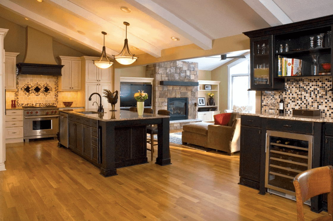 A great room featuring hardwood flooring and a shed ceiling with beams on the kitchen area lighted by gorgeous pendant lights.