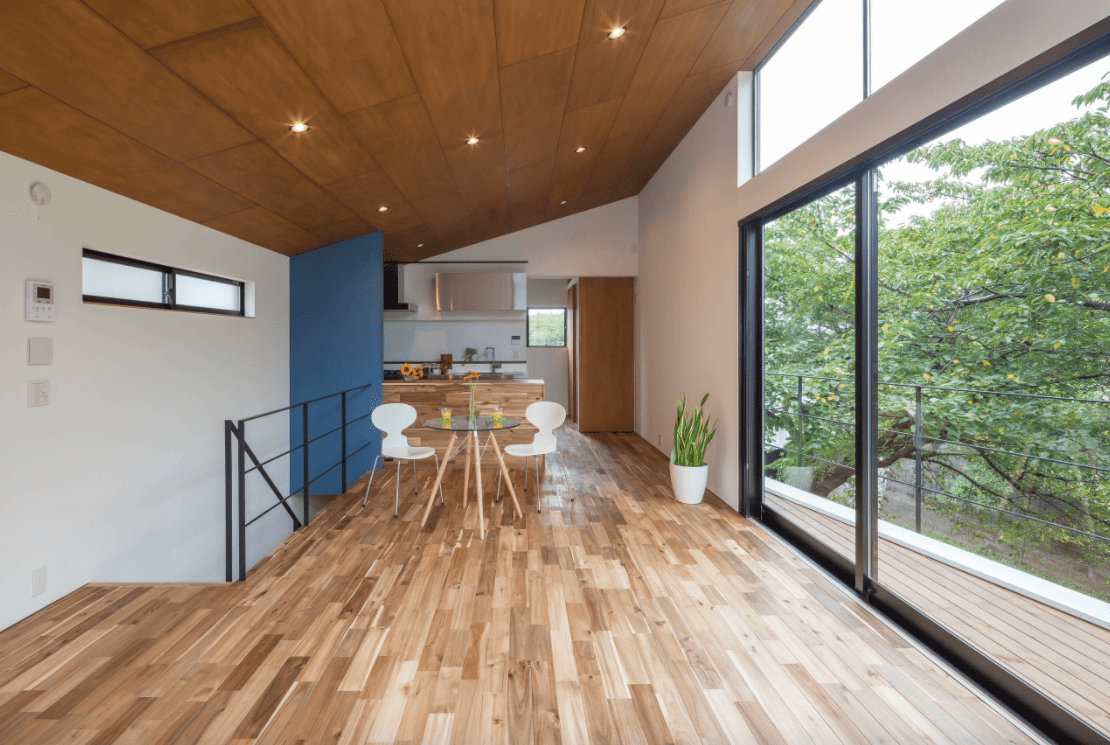 A kitchen set on the home's second floor, featuring hardwood flooring and a high shed ceiling.