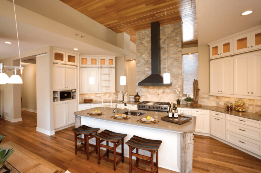 This large kitchen area boasts a high ceiling where pendant lights are hanging. The tiles walls add class to the room. There's a large center island as well providing space for a breakfast bar.