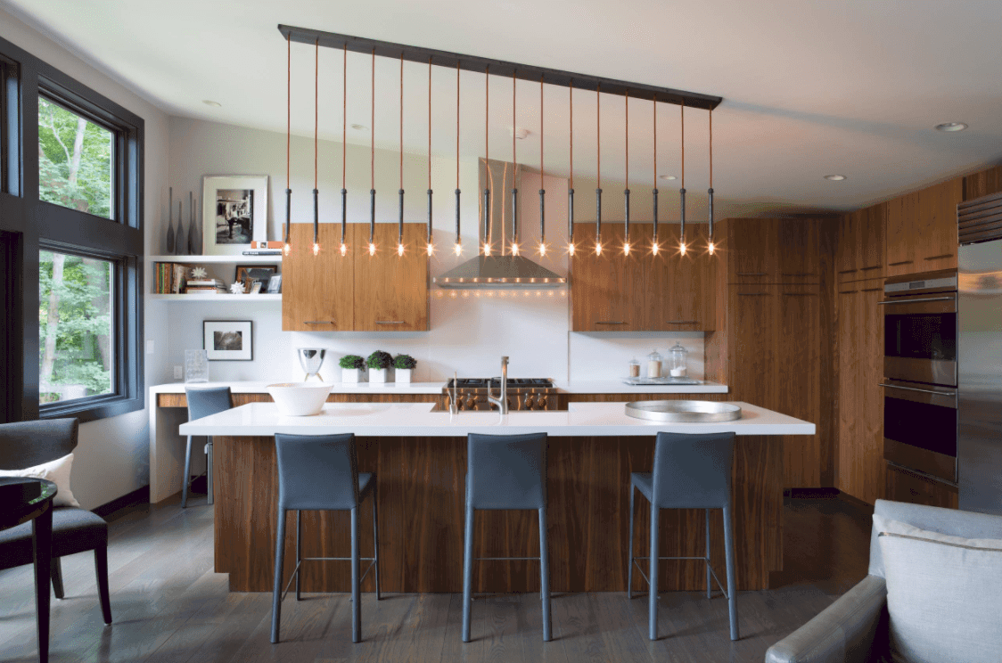 L-shape kitchen with a stunning set of pendant lights hanging from the shed ceiling. There's a large center island providing space for a breakfast bar.