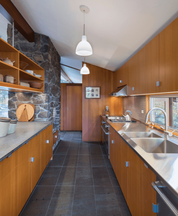 This kitchen features stylish black floors and a white shed ceiling lighted by pendant lights.